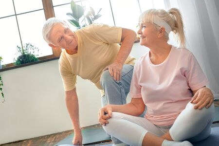 Senior couple doing yoga together at home health care butterfly pose looking on each other