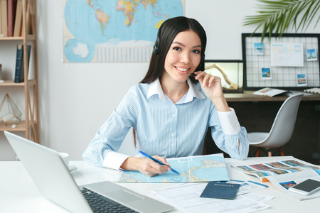 Young female travel agent consultant in tour agency working smiling Stock Photo