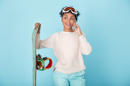 Young african woman isolated on blue wall studio winter sport snowboarding concept phone call