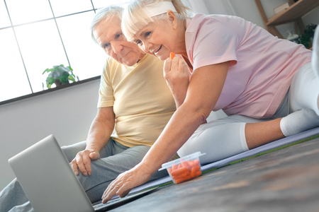 Senior couple exercise together at home health care watching video concentrated