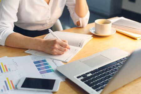 Pregnant business woman working at office motherhood sitting taking notes in organizer