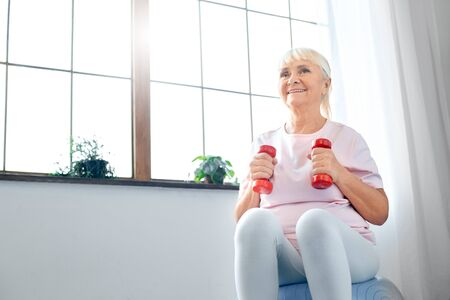 Senior woman exercise at home sitting on exercise ball with dumbbells