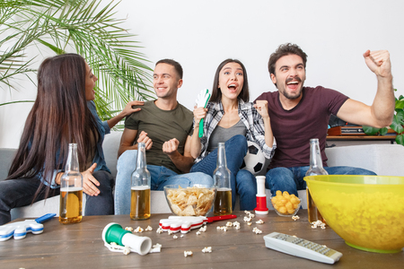 Group of friends sport fans watching soccer match screaming excited