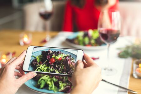 Young couple having romantic dinner in the restaurant salad photos close-up