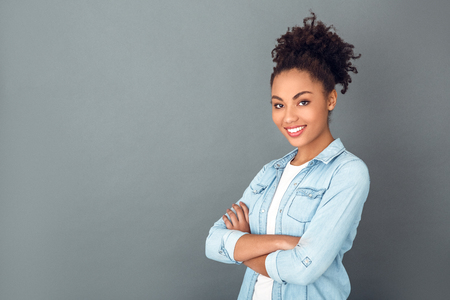 Young african woman isolated on grey wall studio casual daily lifestyle confident