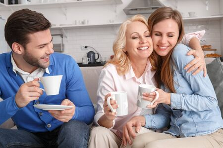 Young family with mother-in-law at home weekend drinking coffee 스톡 콘텐츠