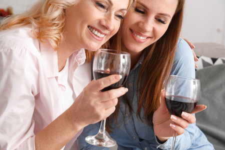 Mother and daughter together at home weekend hugging drinking wine