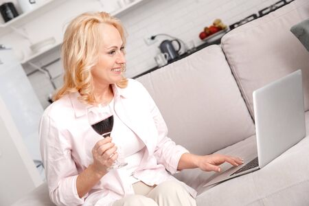 Middle-aged woman leisure weekend at home drinking wine browsing laptop