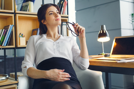 Pregnant business woman working at office motherhood sitting thoughtful