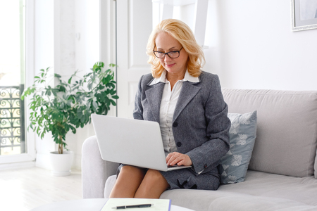 Woman psychologist portrait sitting at casual home office working on laptop