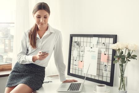 jeune femme pigiste intérieur bureau concept de maison style formel assis sur un bureau en utilisant un smartphone