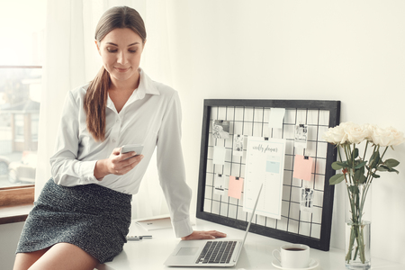 Young woman freelancer indoors home office concept formal style sitting on desk using smartphone Stock Photo - 95144183
