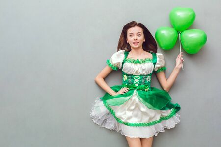 Young woman in a festive dress saint patricks day top view holding balloon
