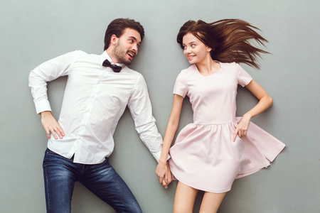 Young couple top view isolated on grey background looking at each other