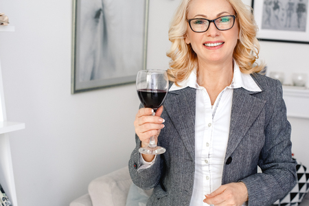Woman psychologist portrait standing at casual home office holding wine glass Stock Photo