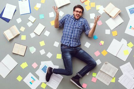 Young man isolated on grey background with papers and notes unsatisfied