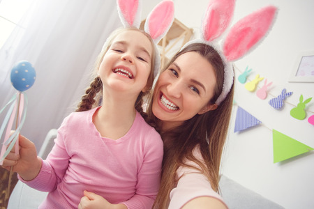 Mother and daughter in bunny ears together at home easter celebration taking selfie photos close-up cheerful 스톡 콘텐츠