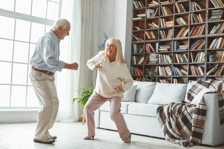 Senior couple together at home dancing actively