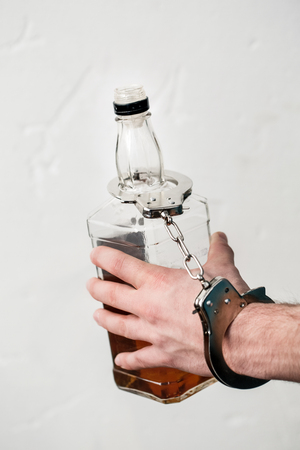Young man at living room alcohol problems holding bottle of whiskey locked with handcuffs close-up