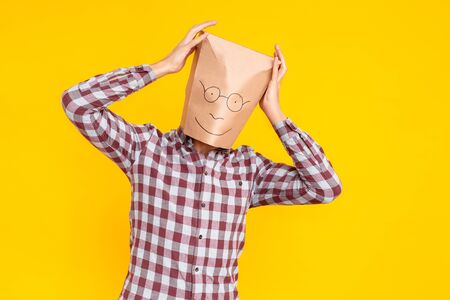 Unknown person with a package on his head. Fool's day emotions and feelings. Indoor shot, yellow background Stockfoto