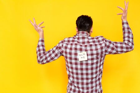 Man does not understand why everyone laughs at him. Stickers on spine. Fools day emotions and feelings. Indoor shot, yellow background