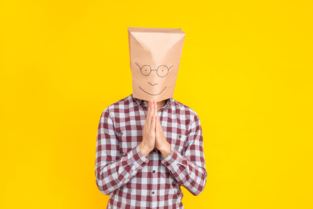 Man with a package on his head, showing please sign, apology. Fools day emotions and feelings. Indoor shot, yellow background