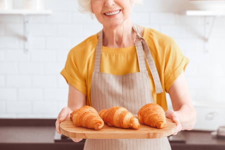Closeup portrait . Homemade sweet pastries. Three ruddy croissants on a platter. Indoor, studio shoot, kitchen interior