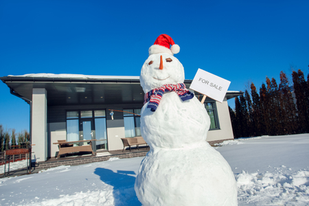 Winter time. Snowman with for sale board and keys on a yard near house no people