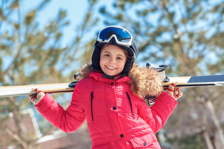 Winter vacation. Girl in goggles and helmet with skis behind standing outdoors smiling excited close-up burred background