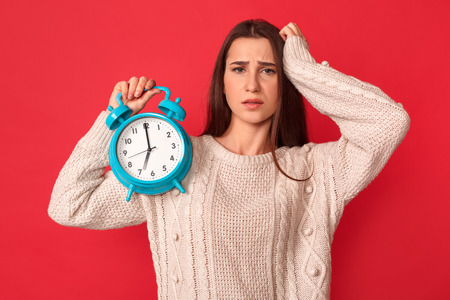 Late for Meeting. Young woman standing isolated on red with alarm clock touching head concerned