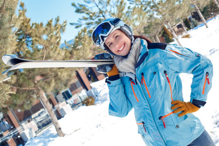Winter vacation. Woman in goggles and helmet standing outdoors with skis posing to camera cheerful