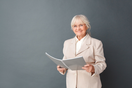Senior woman in fromal suit and glasses studio standing isolated on gray with notebook looking camera positive planning