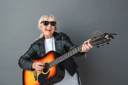 Senior woman in leather jacket and sunglasses studio standing isolated on gray playing guitar smiling