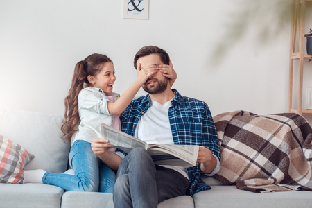 Father and little daughter at home sitting man holding newspaper girl covering his eyes playful