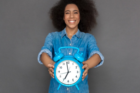 Mulatto woman standing isolated on grey with alarm clock close-up blurred laughing cheerful