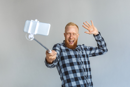 Mature man standing isolated on grey with mono pod taking selfie on smartphone waving to camera friendly