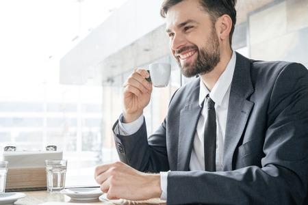 Businessperson on coffee break at restaurant sitting drinking espresso smiling Imagens