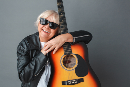 Senior woman in leather jacket and sunglasses studio standing isolated on gray hugging guitar happy close-up