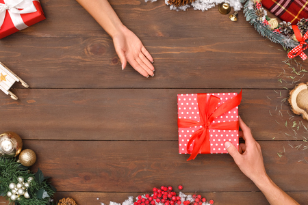 New Year. Man giving present to woman isolated on decorated table top view close-up Stock Photo