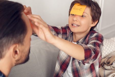 Father and little son at home sitting on sofa playing forehead detective boy sticking paper to dads head excited close-up 版權商用圖片