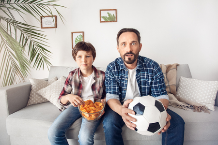 Father and little son at home sitting on sofa boy eating potato chip dad with ball watching soccer looking camera impressed