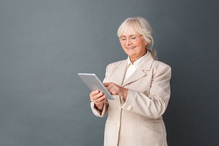 Senior woman in fromal suit and glasses studio standing isolated on gray browsing media on digital tablet joyful Archivio Fotografico - 113822552