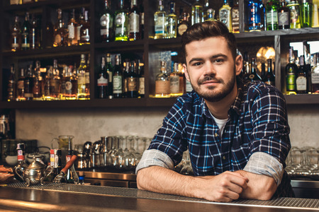 Young bartender leaning on bar counter smiling restrained