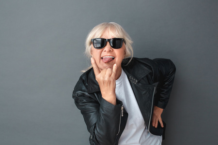 Senior woman in leather jacket and sunglasses studio standing isolated on gray showing tongue through the horns sign cool