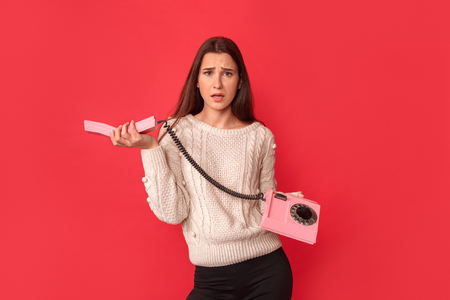 Freestyle. Young woman standing isolated on red with stationary phone handset looking camera concerned