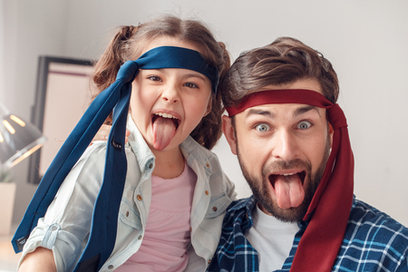 Father and little daughter at home sitting wearing ties tongue out grimace