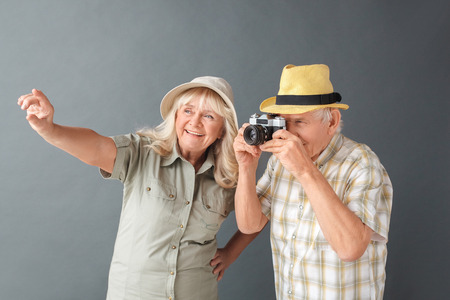 Senior tourists in beach hats studio standing isolated on gray holding camera taking photos cheerful