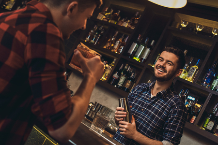 Young bartender standing at bar counter holding shaker talking with customer cheerful