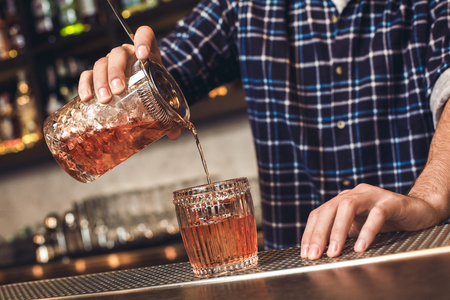 Young barman standing at bar counter pouring cocktail into glass close-up