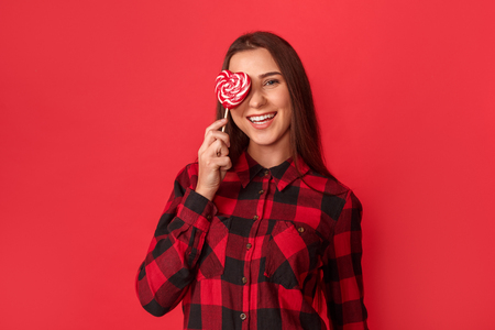 Freestyle. Young girl standing isolated on red covering eye with heart shaped lollipop laughing playful
